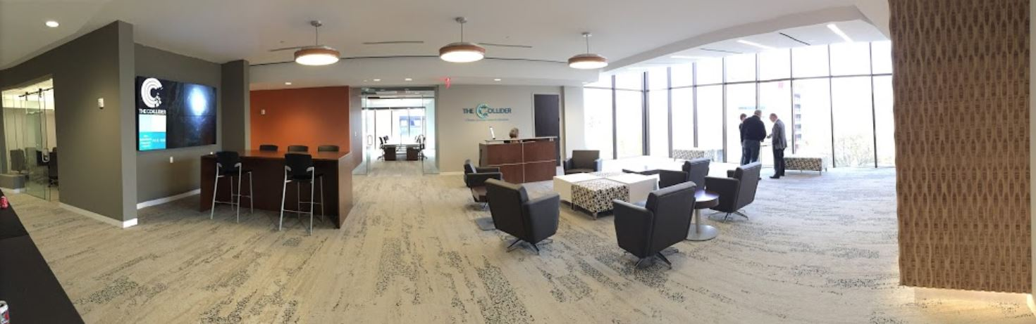 Lobby with Interface Human Nature Carpet Tile, National Fringe Lounge Seating and Ottomans and National Office furniture Staccato Occasional Tables, OFS Element Reception Desk and First Office Intermix Collaborative Table.