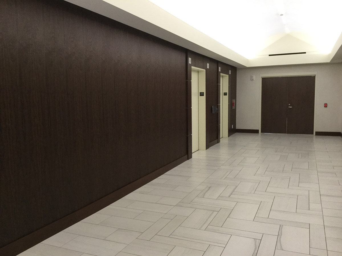 Elevator Lobby with Crossville Moonstruck, SanFoot Mexican Rosewood Natural Wood Veneer Wallcovering and Crossville Laminam Oxide on walls.