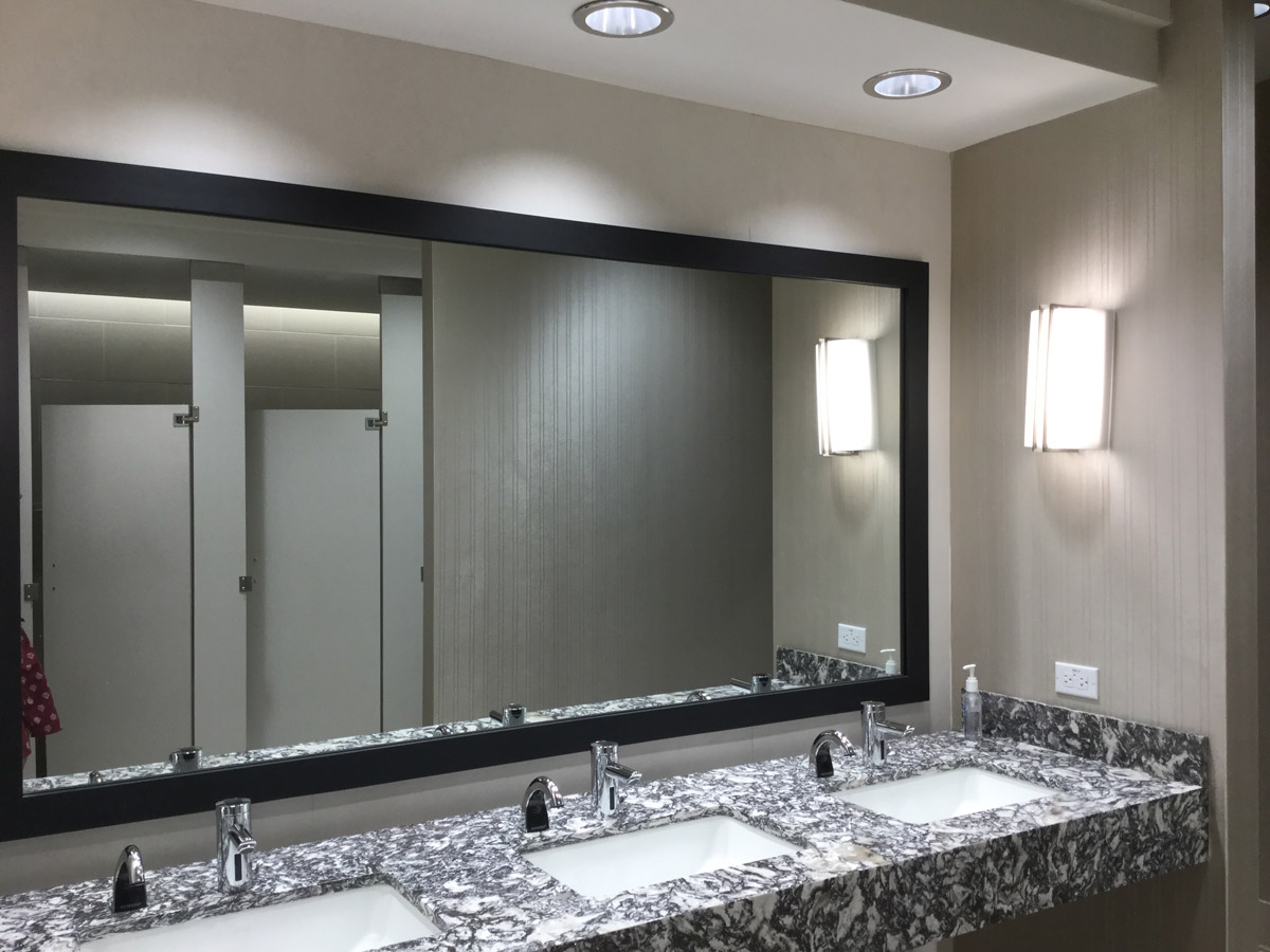 Restrooms with Crossville Quarry Porcelain Tile, Eykon Walk The Line Type II Wallcovering, Kichler Crescent Sconce, Cambria Waterstone Collection Solid Surface, American Specialties Bathroom Accessories and Crossville Laminam Oxide Wall Panels.